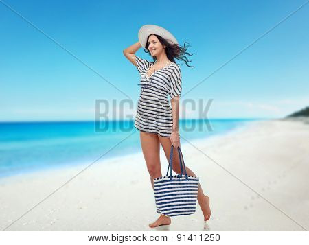 people, fashion, tourism, travel and summer concept - happy young woman in summer clothes and sun hat with bag over beach background