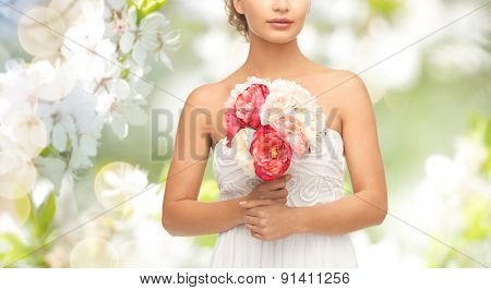 wedding, holidays, people and celebration concept- bride or woman with bouquet of flowers over summer garden and cherry blossom background