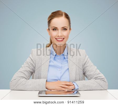 business, technology, education and people concept - smiling businesswoman sitting at table with tablet pc computer over blue background