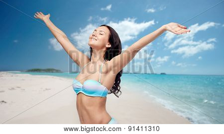 people, tourism, travel and summer concept - happy young woman in bikini swimsuit with raised hands over beach background