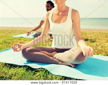 fitness, sport, people and lifestyle concept - close up of couple making yoga exercises sitting on mats outdoors