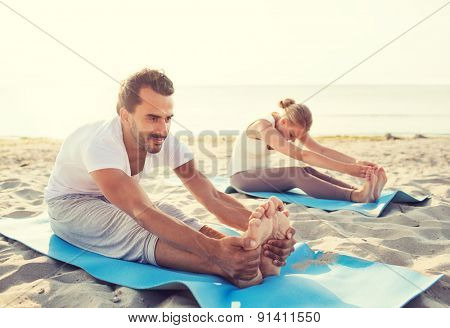 fitness, sport, friendship and lifestyle concept - couple making yoga exercises sitting on mats outdoors