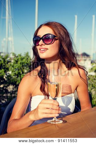 people, summer, drinks and holidays concept - smiling young woman wearing sunglasses drinking champagne on terrace