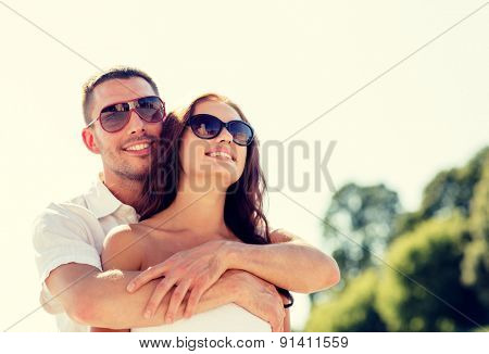 love, wedding, summer, dating and people concept - smiling couple wearing sunglasses hugging in park