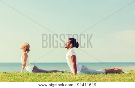 fitness, sport, friendship and lifestyle concept - smiling couple making yoga exercises lying on mats outdoors