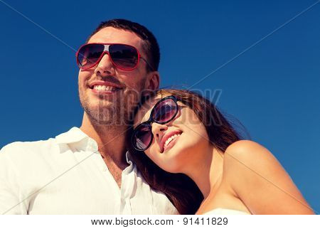 love, travel, tourism, people and friendship concept - smiling couple wearing sunglasses over blue sky background