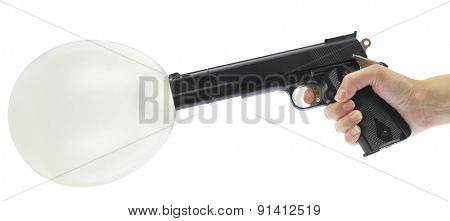 Hand holding gun with balloon isolated on white