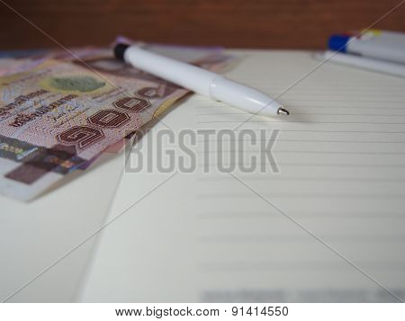 Ballpoint Pen With Banknotes Money On Opened Notebook