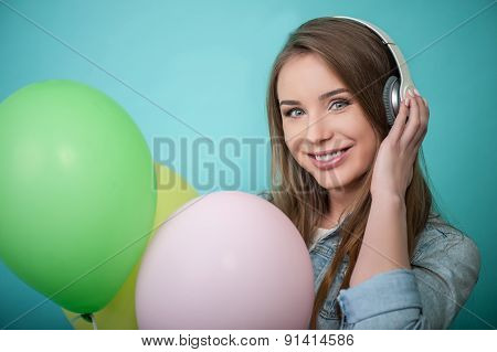 Cheerful Hipster woman with headphones and colorful balloons