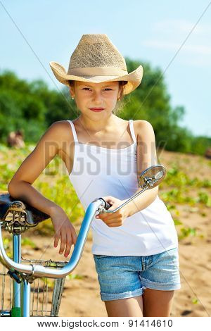 Stylish young girl in casual wear posing with bike