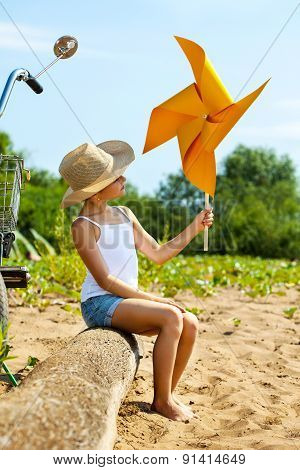 Adorable girl playing with paper windmill