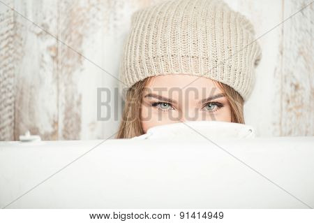 Cheerful hipster woman with valise near the wall