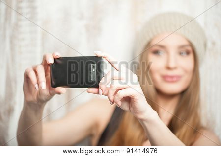 Cheerful hipster woman is making selfie on her phone