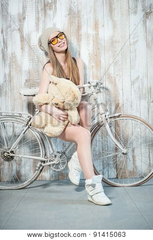 Beautiful hipster woman with toy is on the bicycle