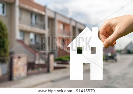 Hand Holds Cut Out Paper House As Symbol For Real Estate
