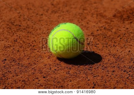 Tennis ball at red clay court