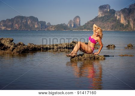 Blonde Girl In  Pink Swimsuit Sits On Stone