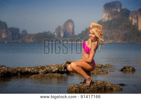 Blonde Girl In Swimsuit  Smoothes Hair On Stone