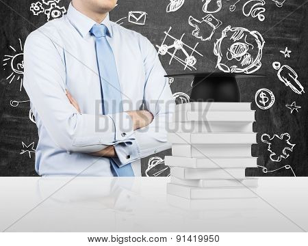 Student With The Crossed Hands Is Standing In Front Of The Books And A Graduation Hat. Educational I