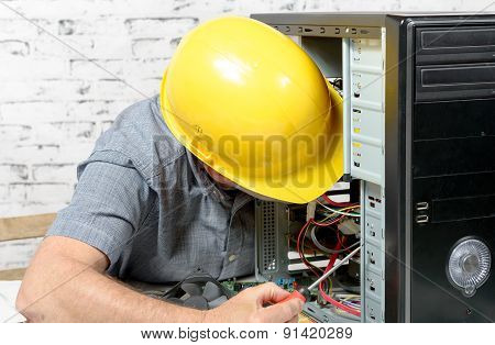 A Technician Repairing A Computer With Yellow Helmet