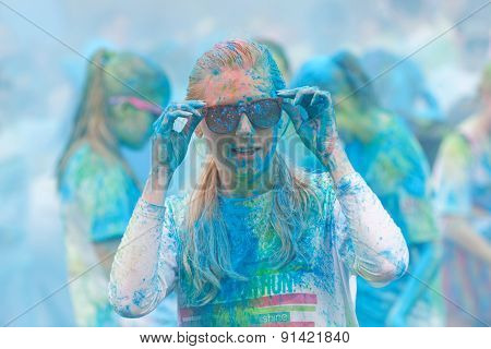 Young Woman Covered With Blue Color Powder Fixing The Glasses
