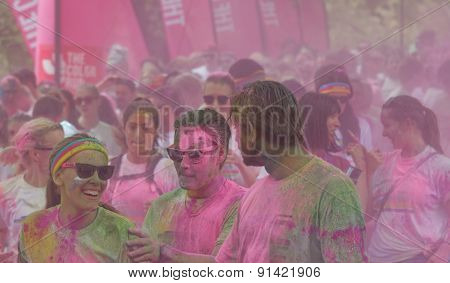 Woman And Men Covered With Pink Color Powder Walking