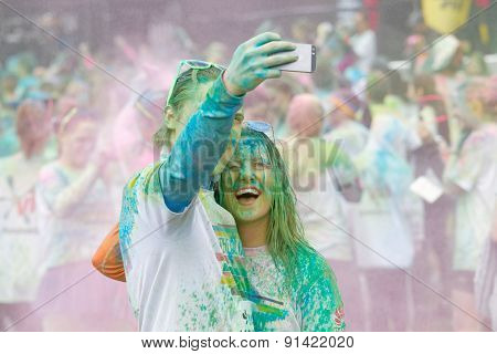 Happy Couple Covered With Blue And Green Color Powder Taking Selfie