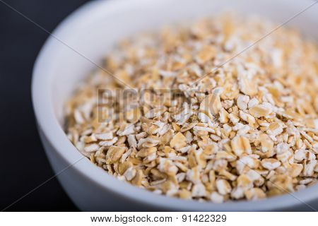 Oatmeal Flakes In A White Bowl On A Black Background