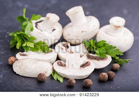 Button Mushrooms And Fresh Parsley On A Black Background