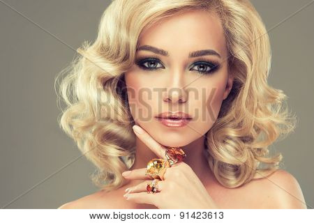 Beautiful cute girl with blonde curly hair with  large rings on her  hand