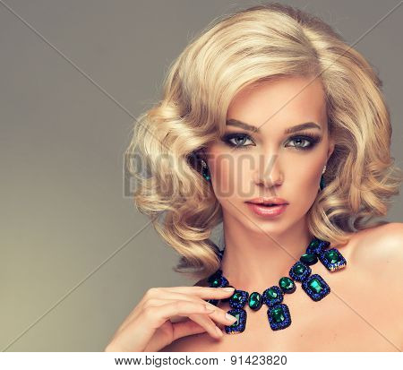 Beautiful cute girl with blonde curly hair with a necklace of precious stones