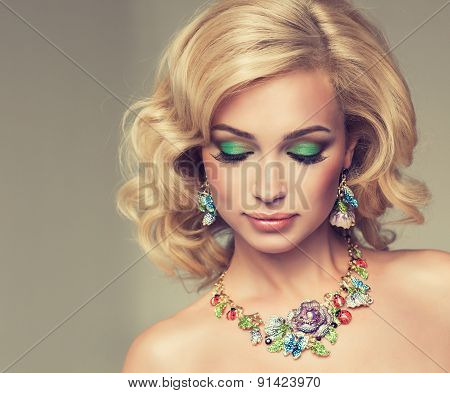 Beautiful cute girl with blonde curly hair with  bright jewelry necklace and earrings