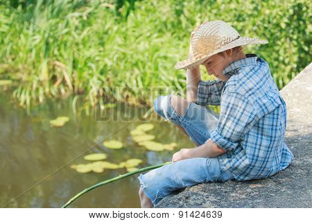 Teenager angler looking down at water from concrete bridge
