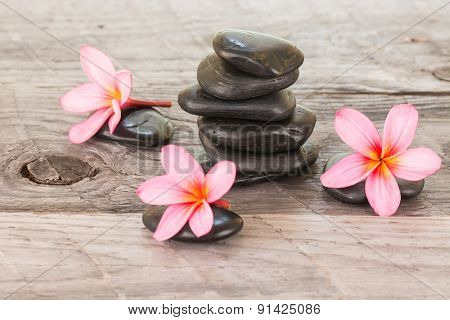 Plumeria Flowers And Black Stones On Weathered Wood