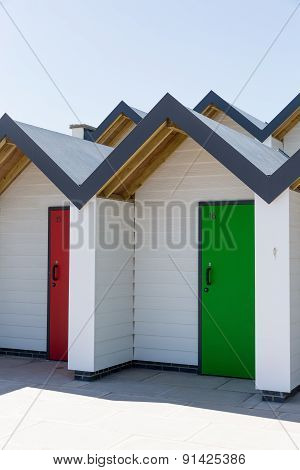 Colourful Doors Of Green And Red, With Each One Being Numbered Individually, Of White Beach Houses O
