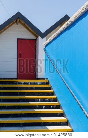 Colourful Red Door, With Each One Being Numbered Individually, Of White Beach Houses On A Sunny Day,