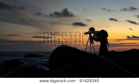 Silhouettes of landscape photographer.