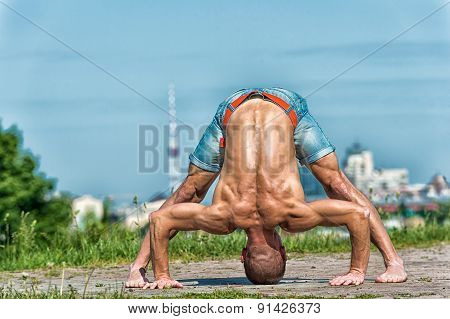 Athletic Man Doing Yoga Asanas In The Park At Sunny Day