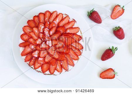 Gourmet homemade party strawberry sponge cake with whipped cream and fresh strawberries on white kit