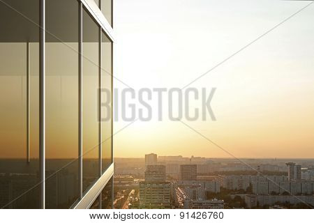 Reflected In The Glass Of An Office Building At Sunset