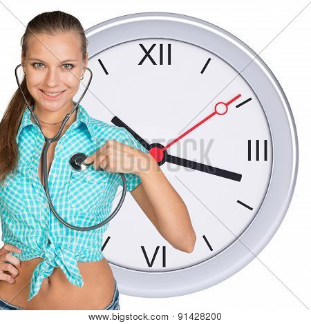 Young woman with stethoscope and clock