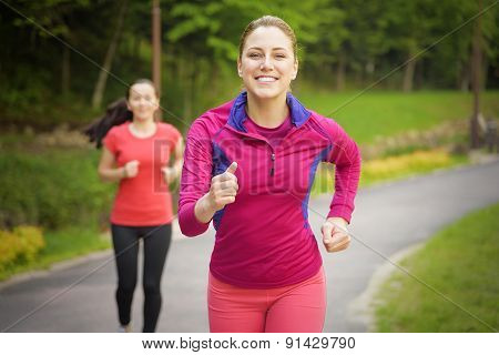 Smiling Friends Running Outdoors.