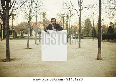 A Man Holding A Empty Blank White Paper Poster Or Board At City Backgound
