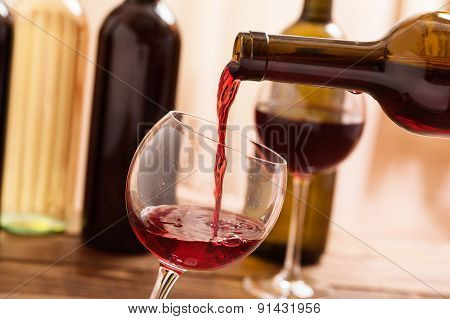 Red wine pouring into glass, close-up.