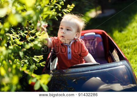 Young Curious Kid With Toy Car Outdoors.