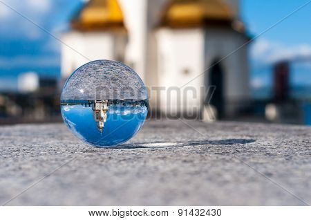 Glass transparent ball on church background and grainy surface. With empty space