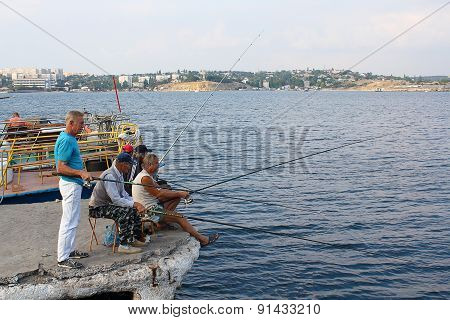 Ukraine, Sevastopol - September 04, 2011: Men Go Fishing In The Afternoon At The City Wharf