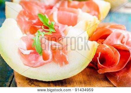 Melon With Thin Slices Of Prosciutto And Arugula Leaves