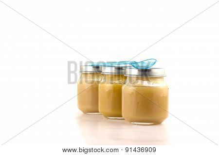 Three jars of fruit puree with a plastic spoon