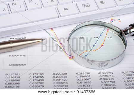 Hand glass on documents with graphs